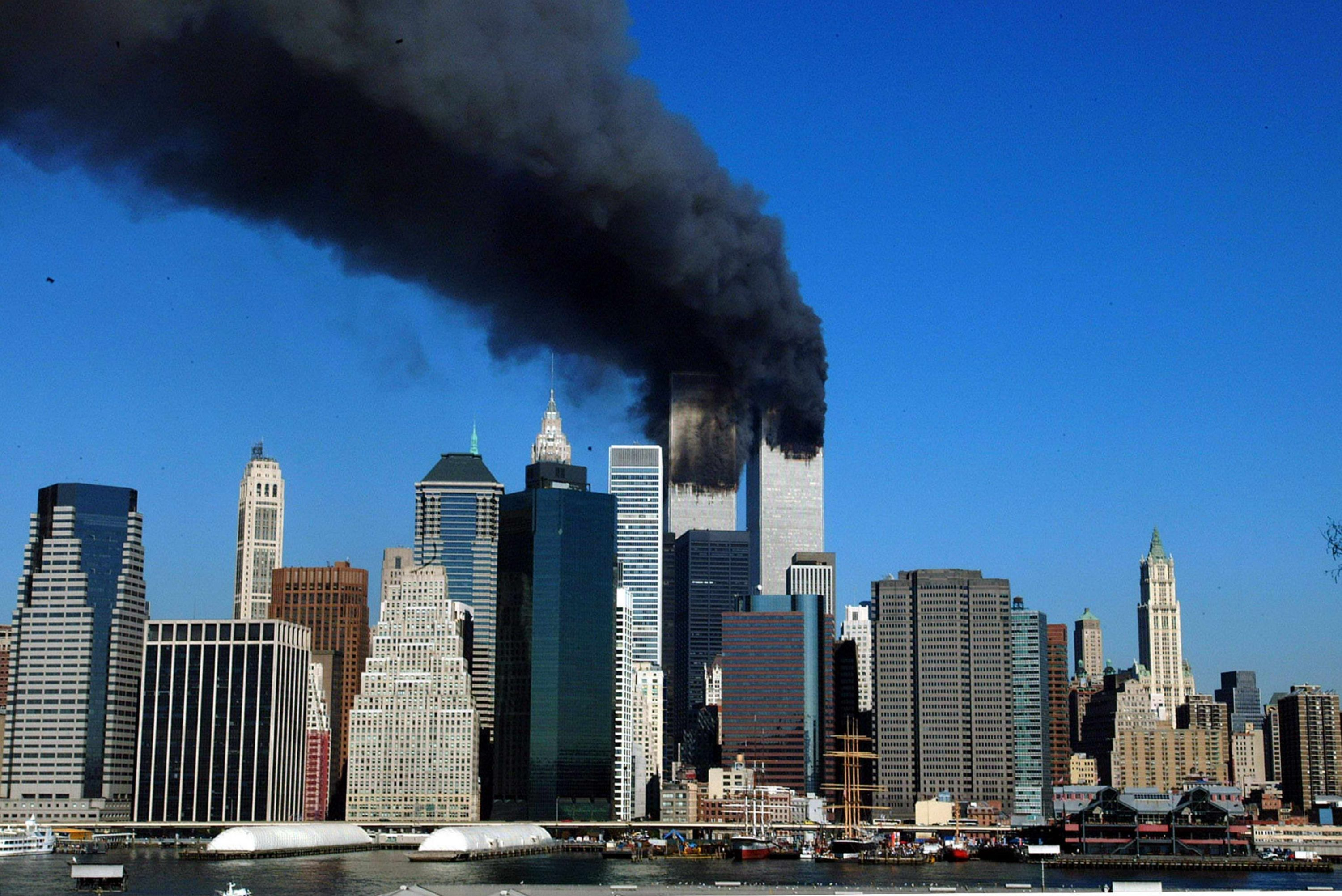 The twin towers of the World Trade Center billow smoke after hijacked airliners crashed into them early 11 September, 2001. The suspected terrorist attack has caused the collapsed of both towers. AFP PHOTO/Henny Ray ABRAMS (Photo credit should read HENNY RAY ABRAMS/AFP via Getty Images)